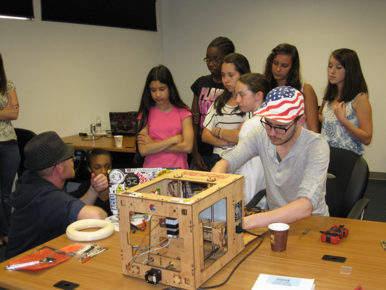 Photo of MakerBot employee showing girls how to build 3D printer